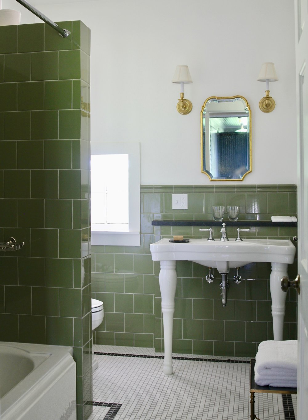 Carriage House Cottage   Moss green tiles adorn the bathroom here. A cast iron tub with shower, and radiant heated mosaic tile floors add a bit of elegance. Toiletries by   Aesop  .