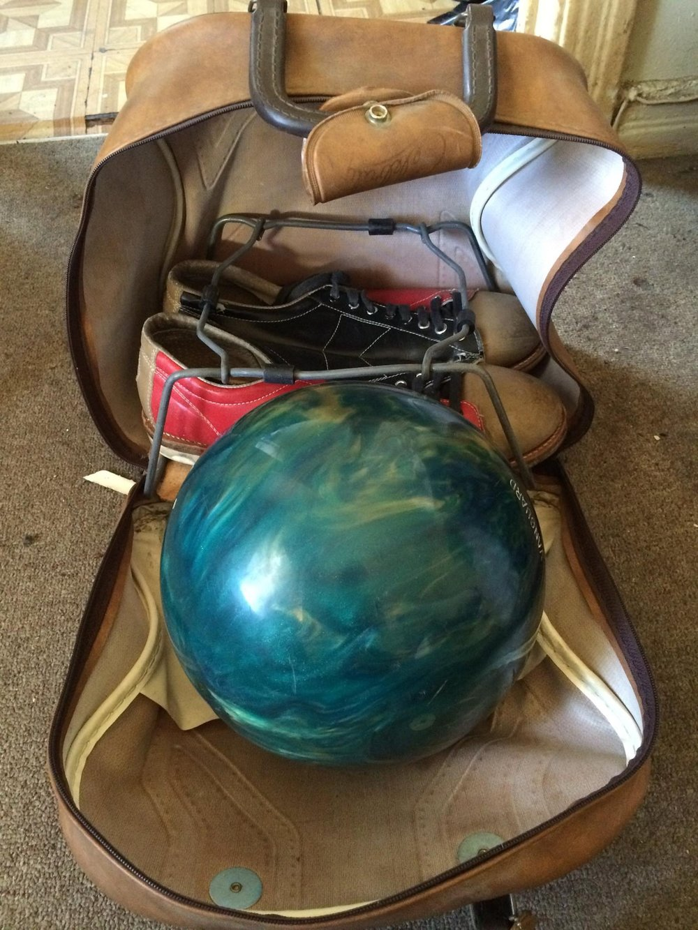 Of everything we've given him and he's lost, ruined or given back, this is the single thing Nick kept safe and in perfect condition. It is the vintage bowling ball and shoes Craig gave him for his sixteenth birthday. He insisted on carrying them on the plane.