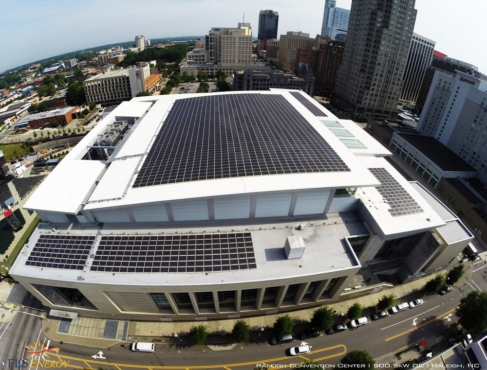 Raleigh Convention Center - The Convention Center project was developed in 2012 without requiring any capital investment from the city of Raleigh. Instead, the City simply leased their roof space for  the solar installation. Solar investors provided the financing for the installation and the power is sold to Duke Energy. This a now a common model for development of solar farm projects and commercial projects. photo courtesy of FLS Energy