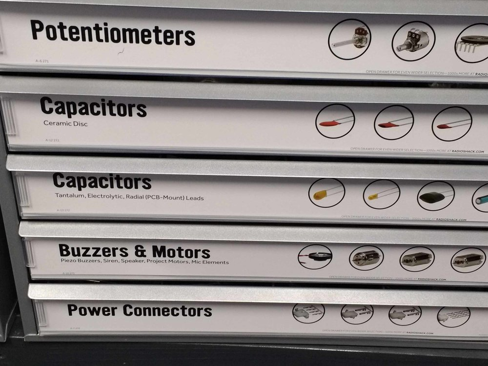 Drawers of potentiometers, capacitors, buzzers & motors, and power connectors.