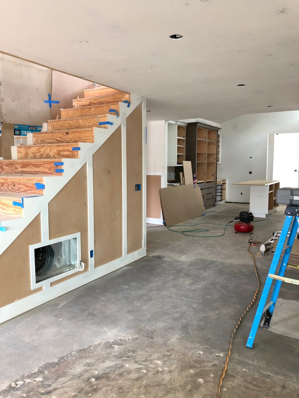 Here is almost the same view. We did a fun paneling that continues up the new staircase and you can catch a glimpse of one of the kitchen islands and pantry.