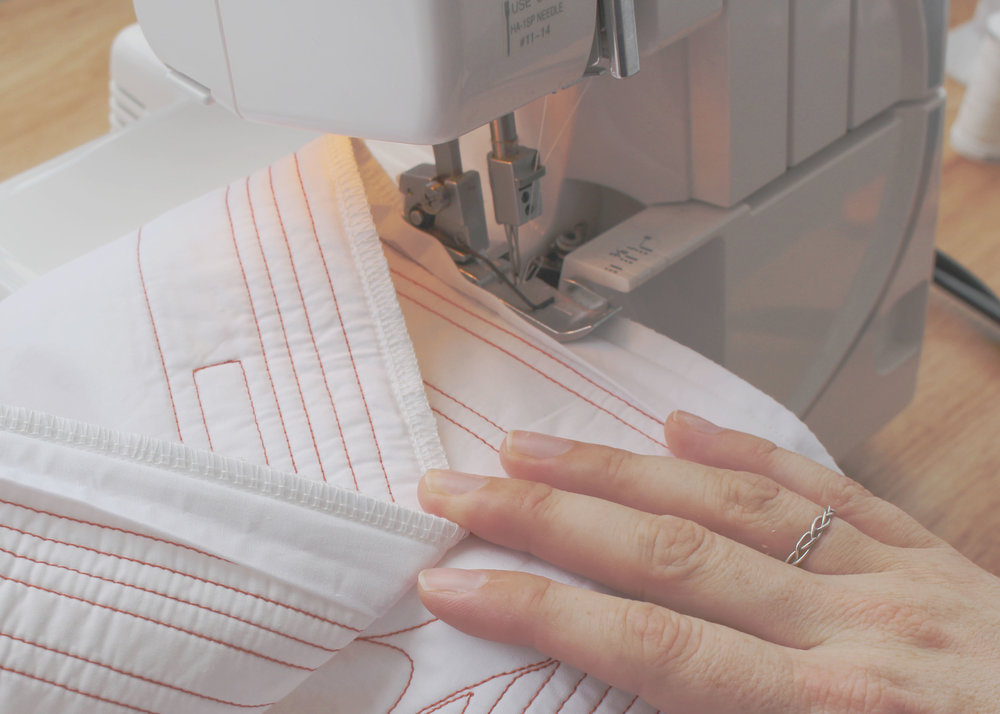 Overlocking - Once quilted, I cut down every quilt to size then sew on the binding. Before hand binding, I overlock all the edges. This gives that little bit of extra security that it will all stay together with long term use.