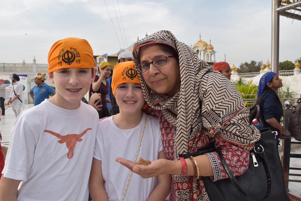 Quentin, Amelia and Sweetie sampling the sweet pudding at Gurudwara Bangla Sahib