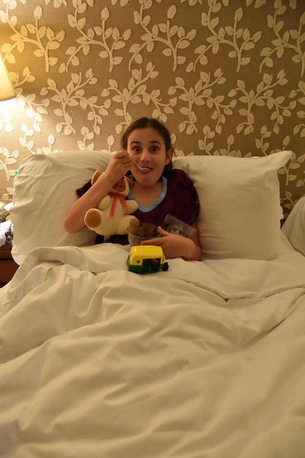 Amelia enjoying chocolate ice cream in bed, which was sent up to her by the restaurant manager (along with a series of gifts) as a surprise