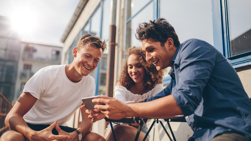 Group-of-friends-watching-video-on-smartphone-599922122_1258x838.jpeg