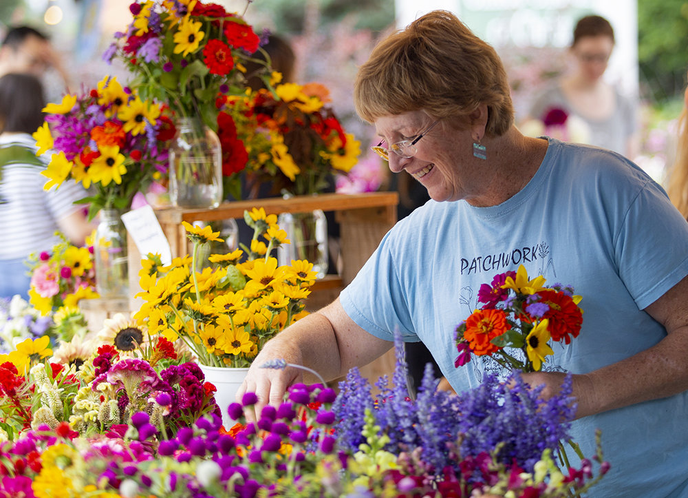 Eda Case of Patchwork Farm laughs as she picks flowers and talks with other vendors at the Downtown State College Farmers Market on Friday, Sept. 21, 2018.