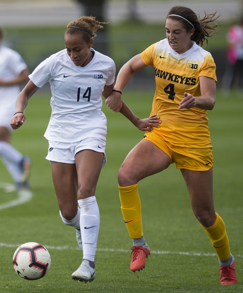 Defender Ellie Jean (14) and forward Kaleigh Haus (4) fight for dominance over the ball during the Penn State v. Iowa women's soccer match at Jeffrey Field on Sunday, Sept. 30, 2018. Penn State defeated Iowa 2-0.