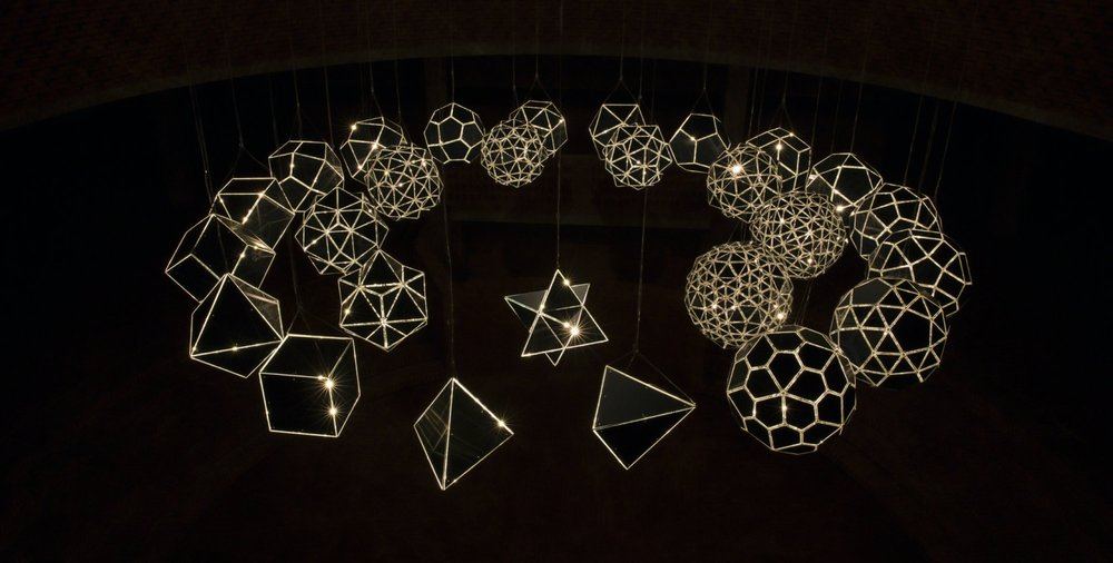 Your Sound Galaxy, 2012, is a group of twenty-seven polyhedra suspended from the ceiling and arranged in two horizontally concentric circles. The polyhedra are arranged in a clockwise sequence in which each form has more faces than the last, leading up to, but never reaching, a sphere. Each form is made of a stainless steel frame clad in mirrored glass that is turned inwards, so that the mirrors' blue-grey versos act as the faces of the polyhedron. A single halogen light bulb mounted inside each polyhedron is multiplied by the reflective interior into a twinkling glow that escapes through the gaps in the frames and gives the sense of a universe contained within. The twenty-seven polyhedra are organisable into nine 'families' of three related forms, in which two of the three are so-called dual polyhedra – meaning that the vertices of one correspond to the faces of the other – and the third, hanging in the inner circle, is created by combining the other two. For example, an octahedron, made from eight equilateral triangles, is combined with its dual, a cube, to form a cube-octahedron. An example of a more complex combination is the pentagonal icositetra–snub cube: the fusion of a polyhedron with twenty-four faces, known as a pentagonal icositetra, with a snub cube, which has twenty-four vertices and thirty-eight faces (six squares and thirty-two equilateral triangles).      The title of the work relates to the theory laid out in Johannes Kepler's The Harmony of the World that the universe is organised according to the rules of musical harmony, where each object in space constitutes a sound, although this sound is not audible. This belief extends as far back as Pythagoras, who, legend has it, theorised that the movement of the planets and stars follows mathematical laws and proportions that correspod to musical notes. Seen in this light, each polyhedron in Your sound galaxy can be understood as a kind of celestial body in a universe that is not chaotic but logically structured.