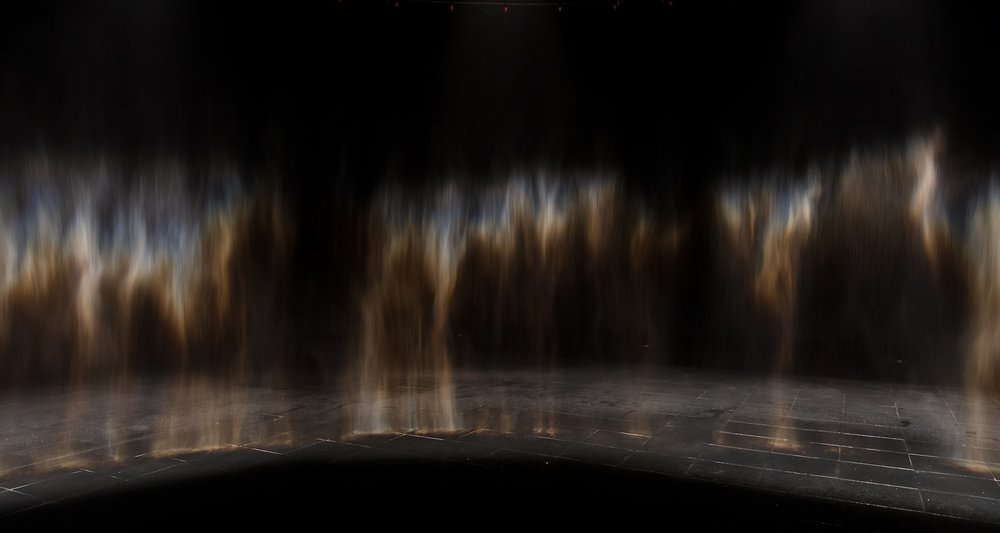 A circular curtain of mist inside a darkened space is illuminated from within by a ring of spotlights that cause shimmering rainbows to appear on the circle's inward-facing side. The shimmering colours visible in the curtain of softly falling water are not present in the mist itself, but are seen there when rays of light are refracted and reflected by the droplets of water and meet a viewer's eye at a particular angle. The work is thus incomplete until someone comes along to close the circuit by moving into a position from which the colours can be seen. Eliasson's works depend on the viewer's engagement; the artist makes frequently use of phenomena like reflections and afterimages that are absent in the artworks themselves but produced when the artwork is viewed. This work is an evolution of one of Eliasson's most important early works: Beauty, from 1993.
