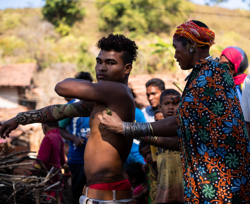 Bonda woman rubs fresh turmeric on her husband's wounds