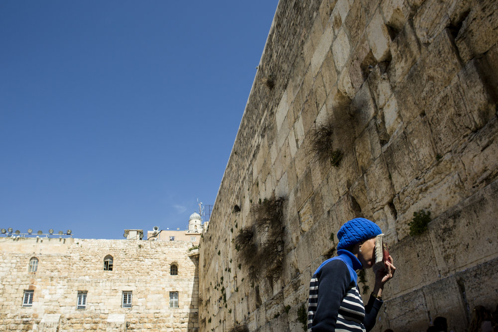 A woman prays in front of The West Wall