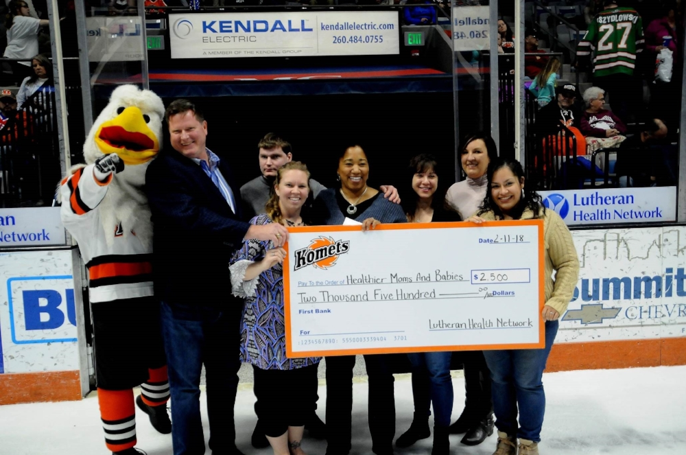 Members of the Komets organization present large check to Healthier Moms and Babies during a period break of a hockey game.