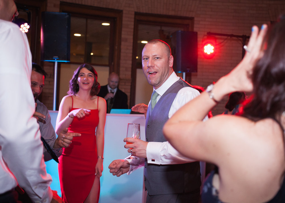 Groom in a gray vest dances with wedding guests in front of a red light at the reception.