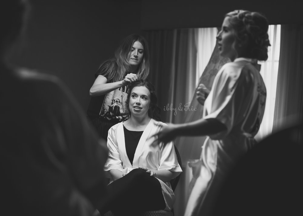 Black and white photo of a hair stylist from Carve Beauty Bar putting the finishing touches on the brides hairstyle.