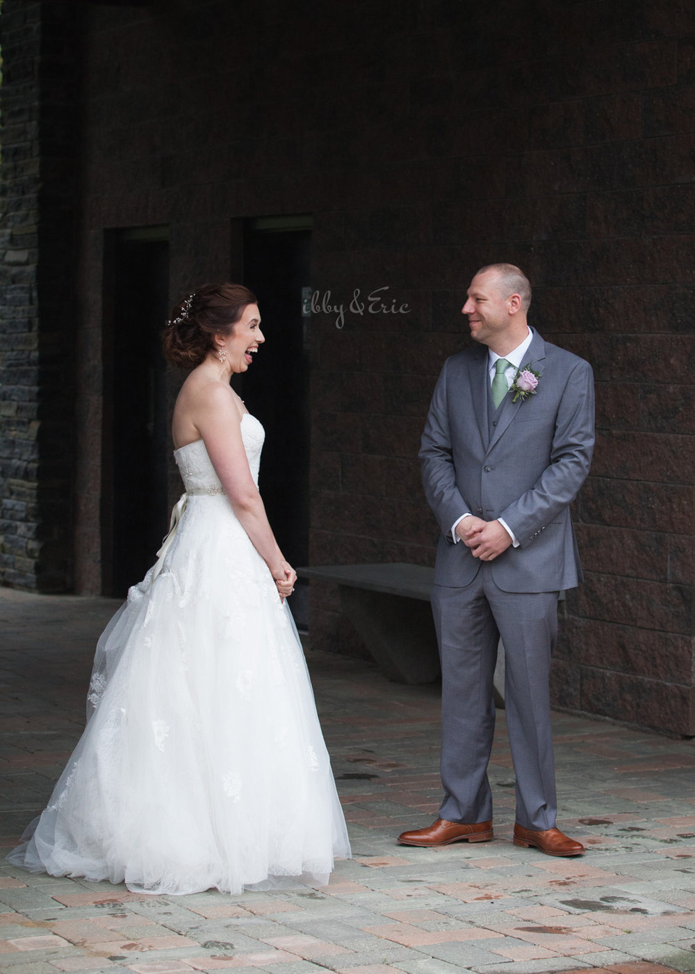 Groom in a gray suit smiles as he sees his bride in a lace wedding gown for the first time.