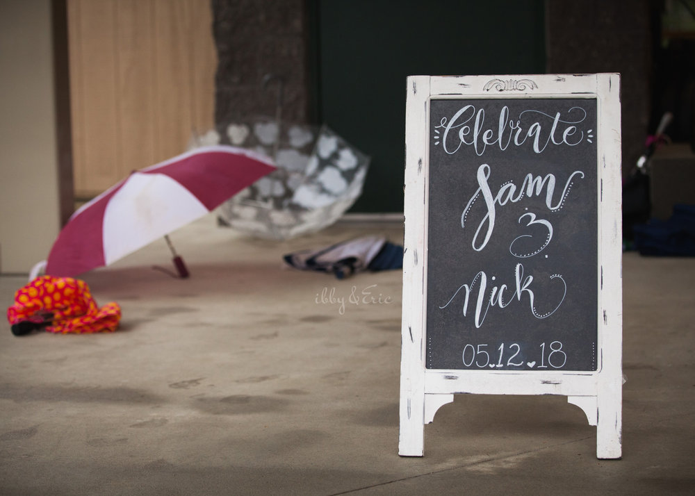 Chalkboard design wedding sign at the Beveridge Pavillion with rain umbrellas in the background.