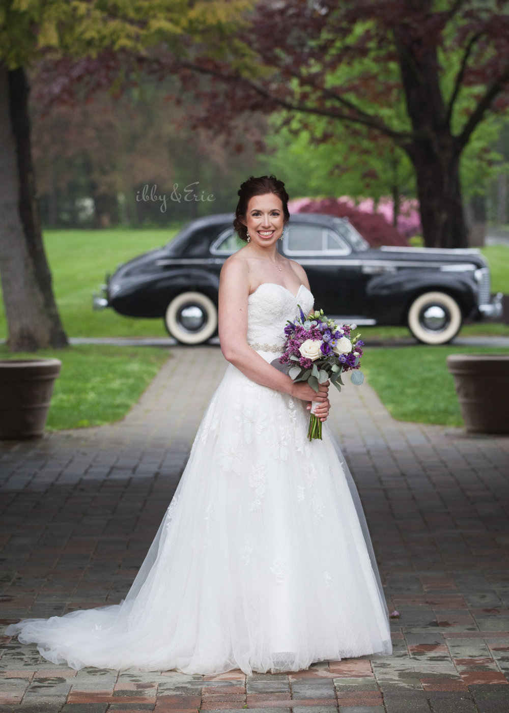 Smiling beautiful bride wearing a white lace wedding gown holds a purple bouquet in front of a vintage car.