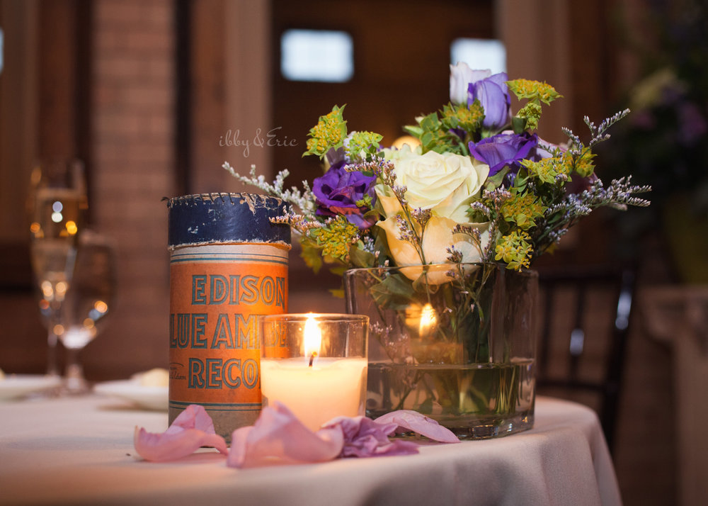 Wedding table centerpiece with edison records, candles, and purple flowers.