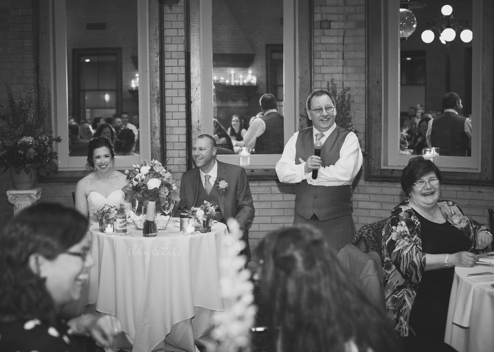 The bride and groom laugh as the best man gives a speech at the Union Station Northampton wedding reception