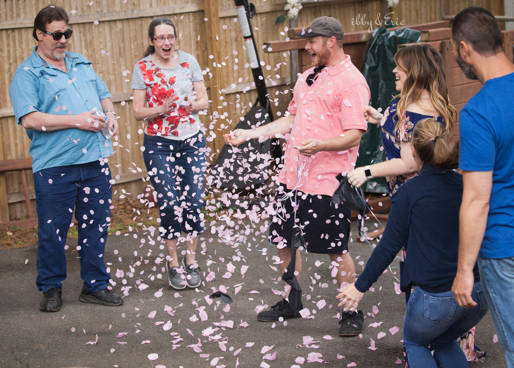 Proud parents celebrate having a baby girl with pink confetti at this western Massachusetts gender reveal party.