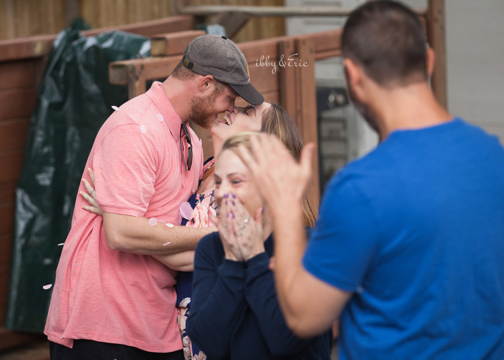 Proud parents kiss and celebrate at a backyard Massachusetts gender reveal party.