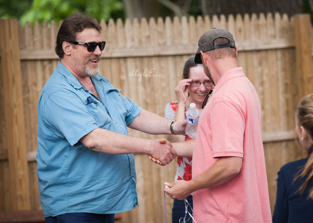 Man in blue shirt shaking hands with his son at a party in western Mass.
