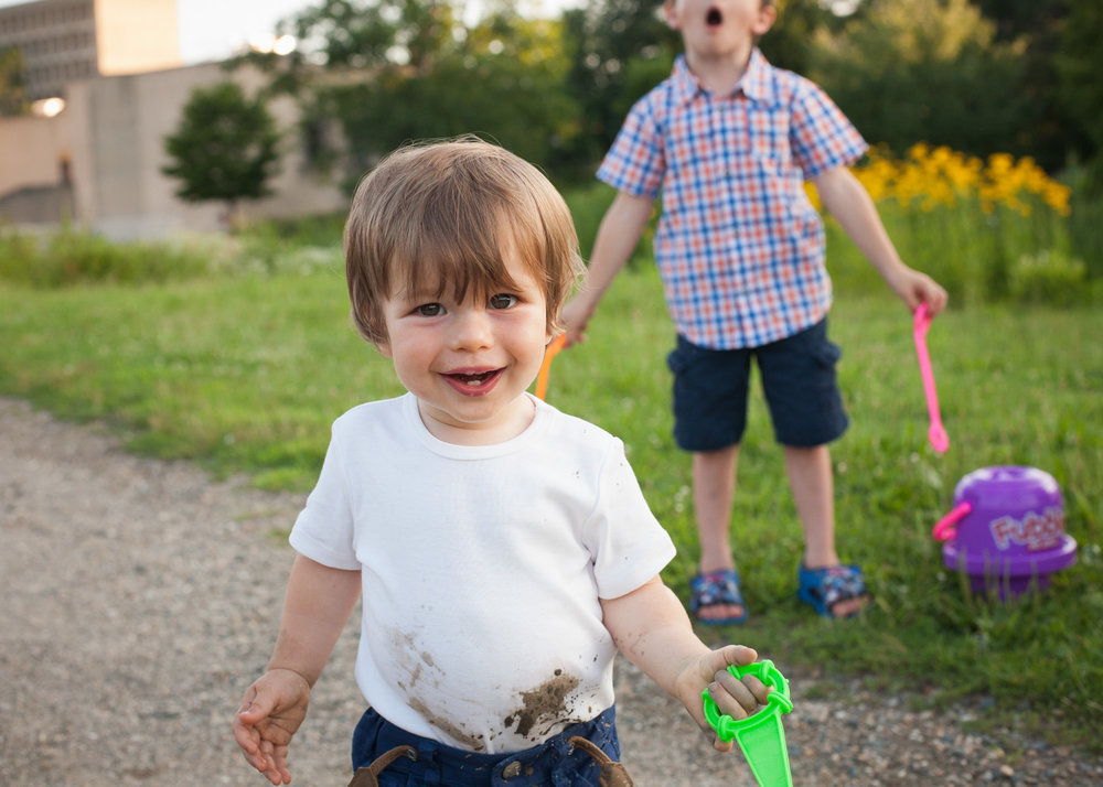 Toddler boy wearing a muddy white tee shirt smiles while his brother looks disappointed in the background.