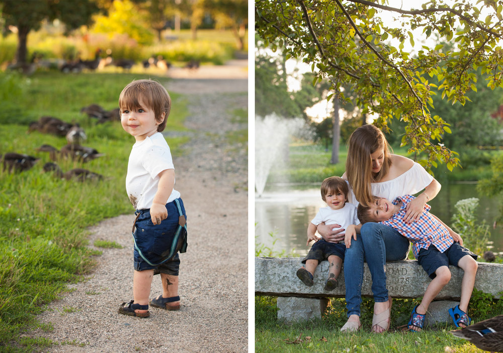 2 year old boy stands in front of ducks in a park. Mom tickles her sons while sitting on a bench in front of a pond.