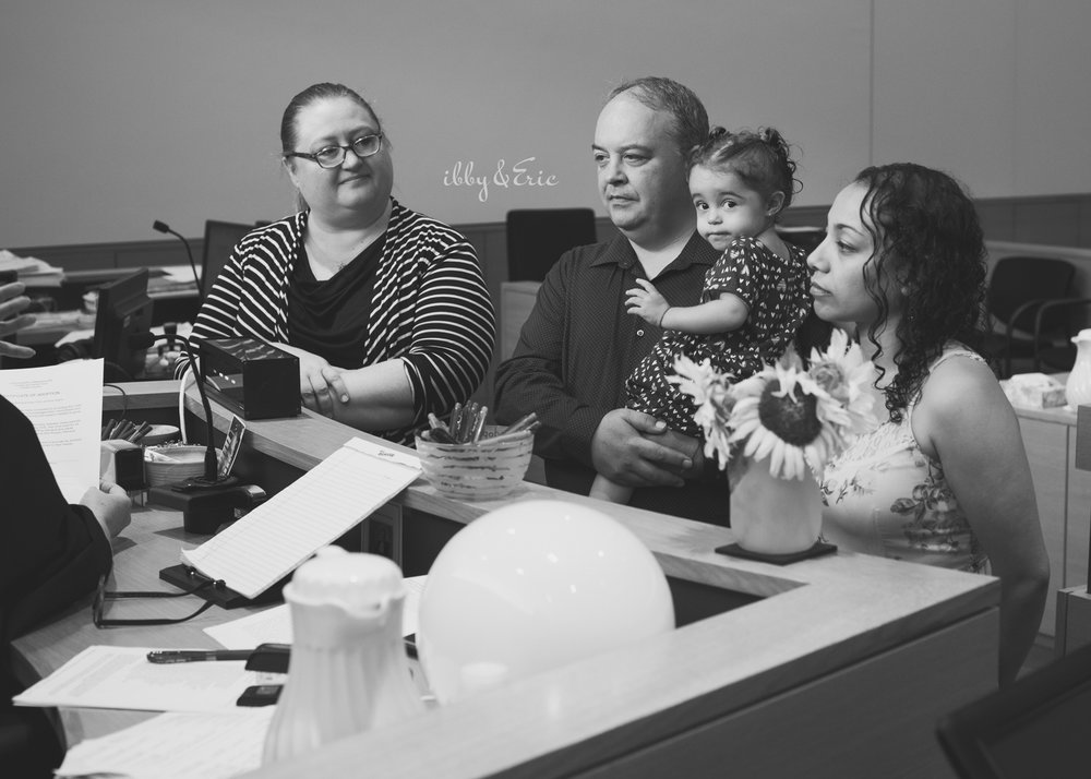 Black and white photo of girl peeking at the camera during her family's adoption in Greenfield courtroom.