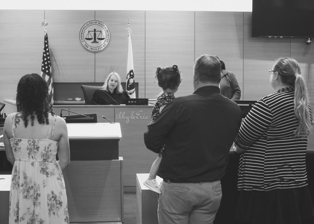 Black and white photo of a family standing before a judge at their adoption ceremony in Franklin County.