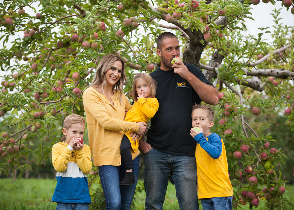 Family of 5 dressed in blue and yellow eat apples at an Easthampton apple orchard.