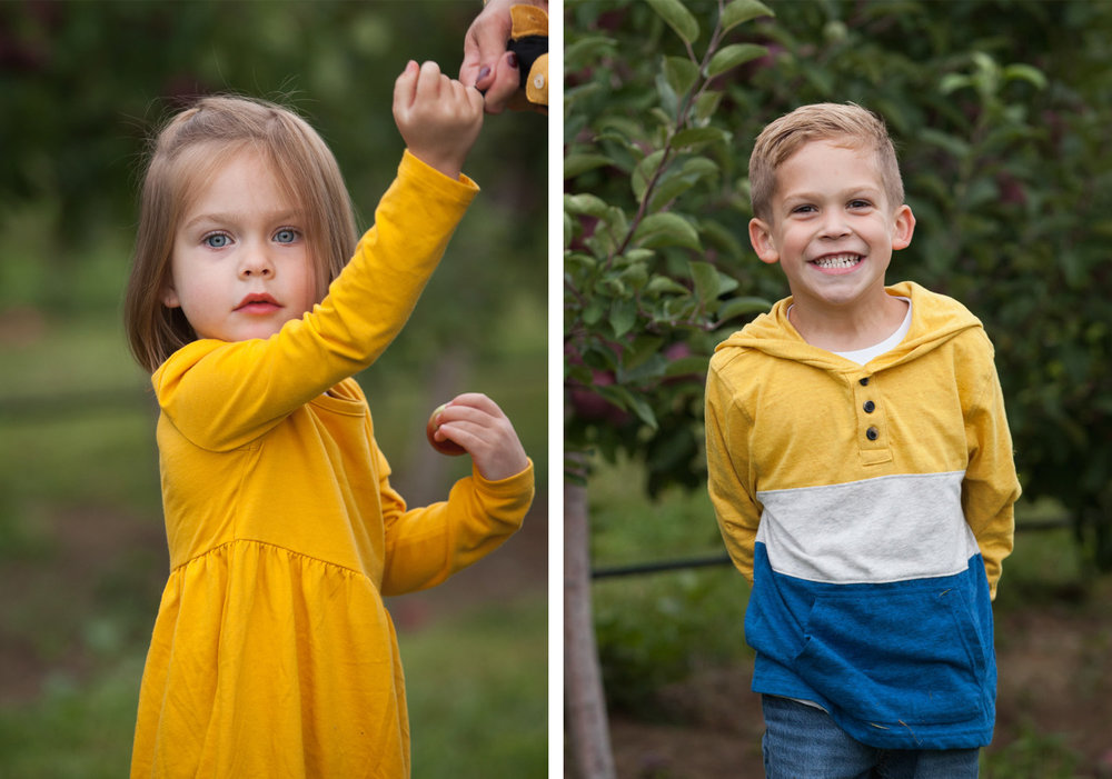 2 year old girl wearing yellow dress holds a tiny apple and boy wearing striped shirt smiles in front of an apple tree.