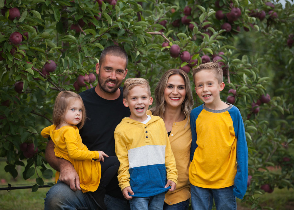 Family of 5, two sons and 1 girl, dressed in yellow & blue hug and smile in front of apple trees