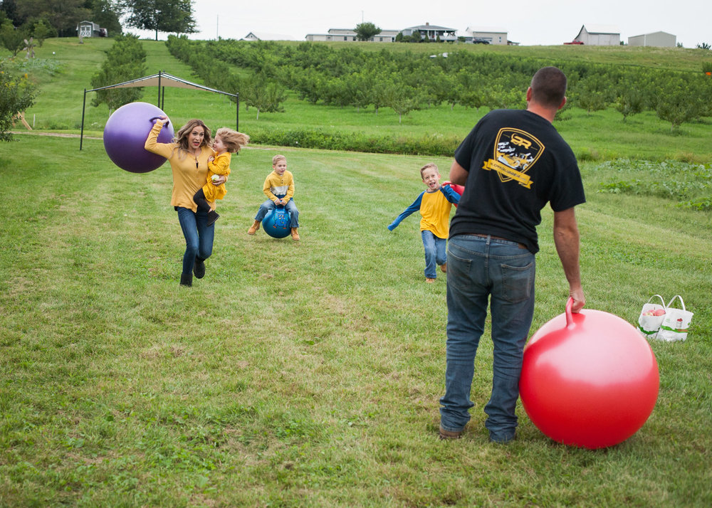 Mom holding her daughter in a yellow dress runs and throws a big bouncing ball at her husband.