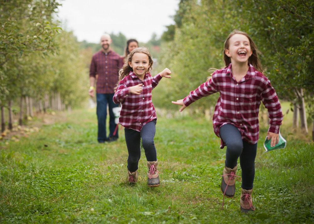 Two girls, wearing plaid shirts and jeans, run towards the camera in a row of apple trees.