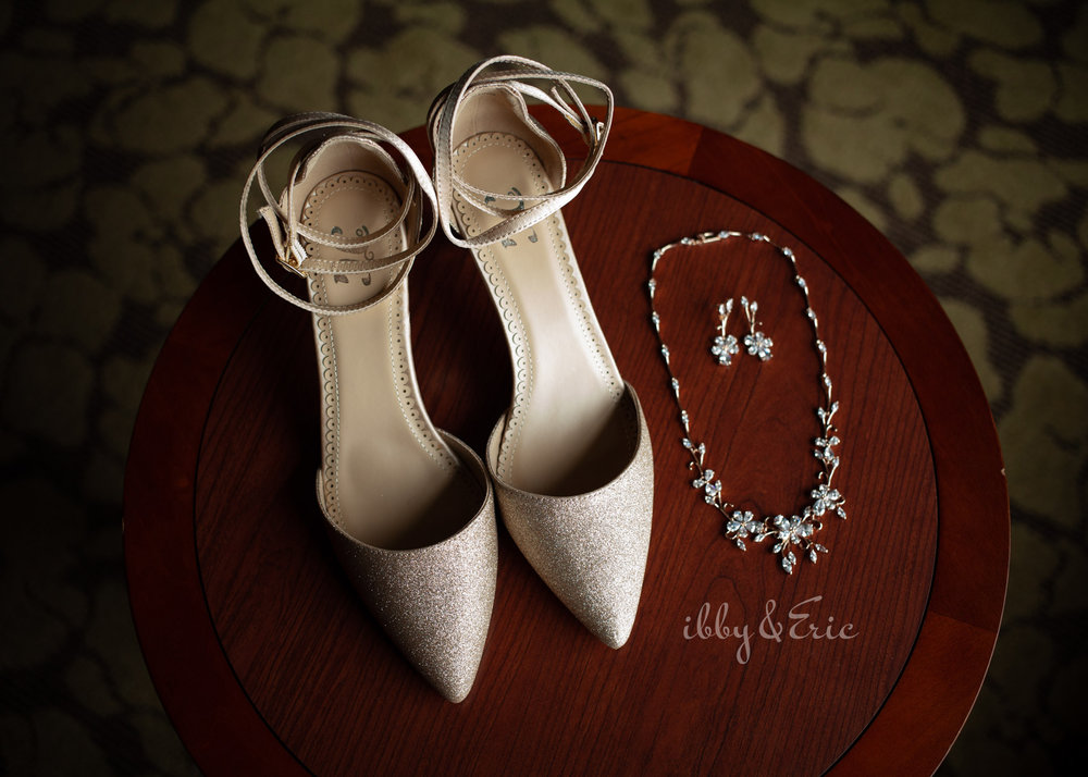 Gold glittery shoes with ankle straps on a wood table with floral necklace and earrings.