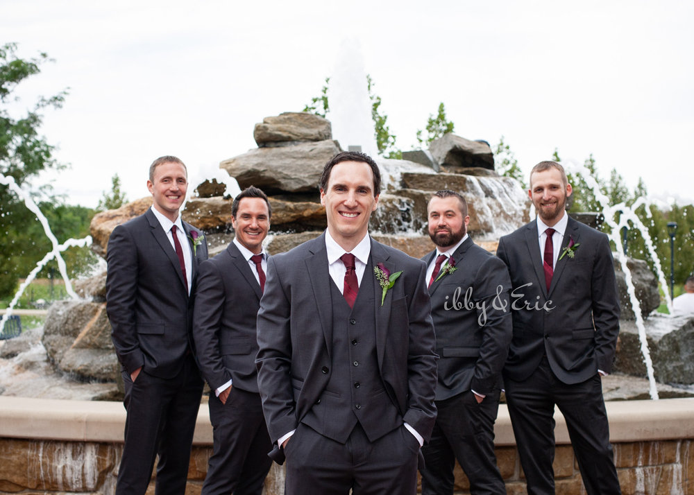 The groom stands in front of a fountain in Glastonbury with his 4 groomsmen wearing black suits with burgundy ties.