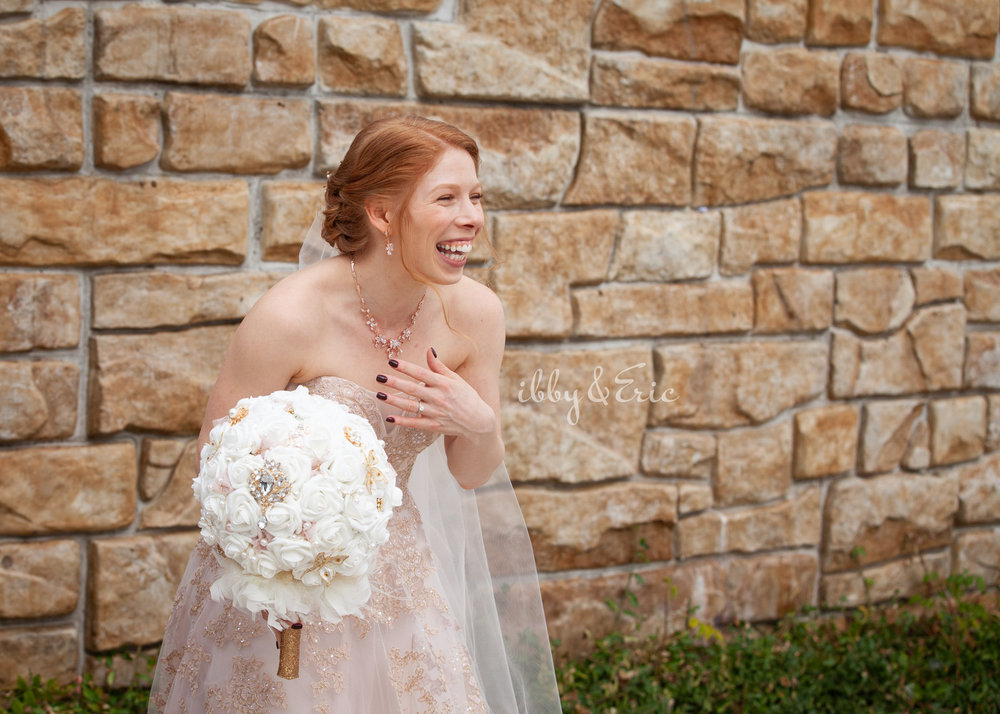 Bride wearing a blush floral wedding gown and a white bouquet laughs outside of the Glastonbury Boathouse.