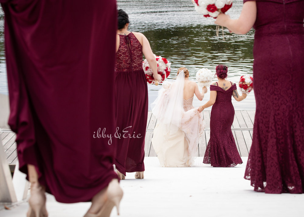 Bride walks down a riverfront dock with her bridesmaids wearing burgundy lace dresses.