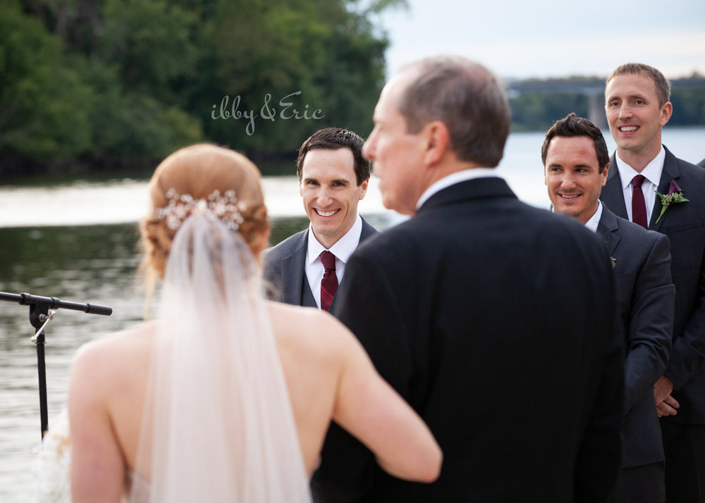 Happy groom smiles when he sees his bride to be for the first time walking down the aisle.