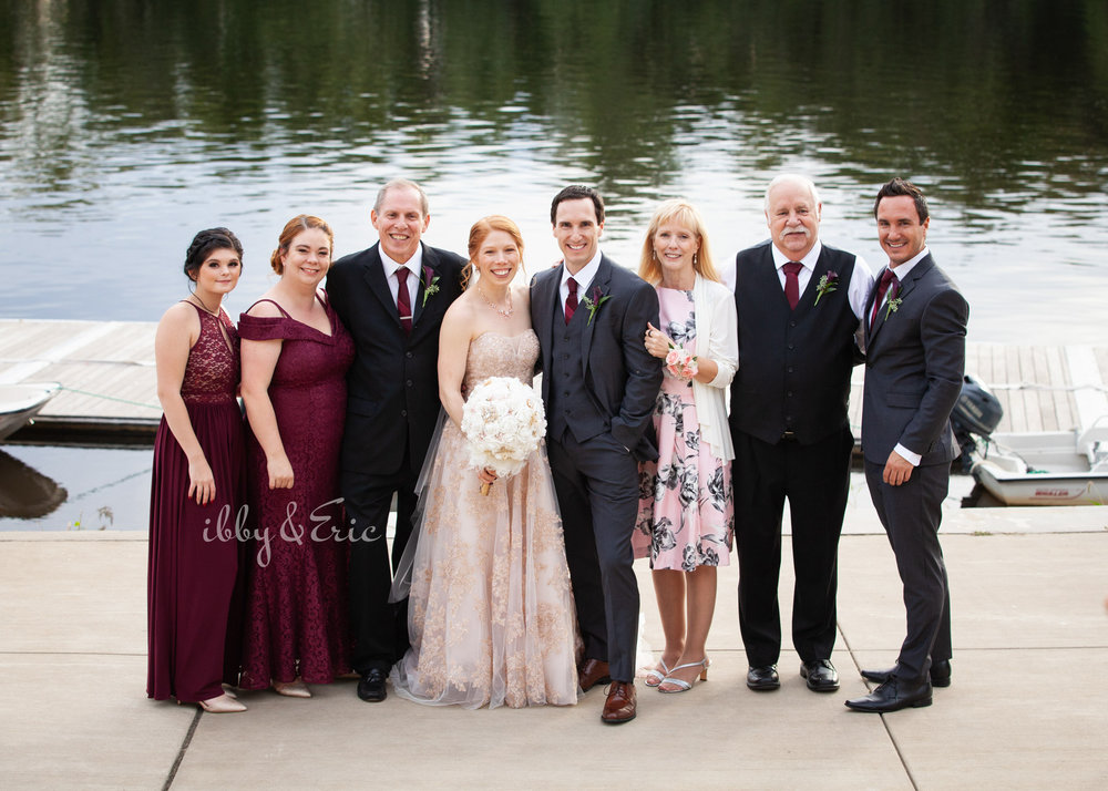 The bride and groom's families stand together by the dock at the Glastonbury Boathouse for a riverfront family photo.