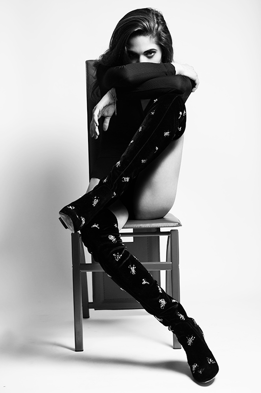 Black and white editorial photography of a model in a studio sitting on a chair.