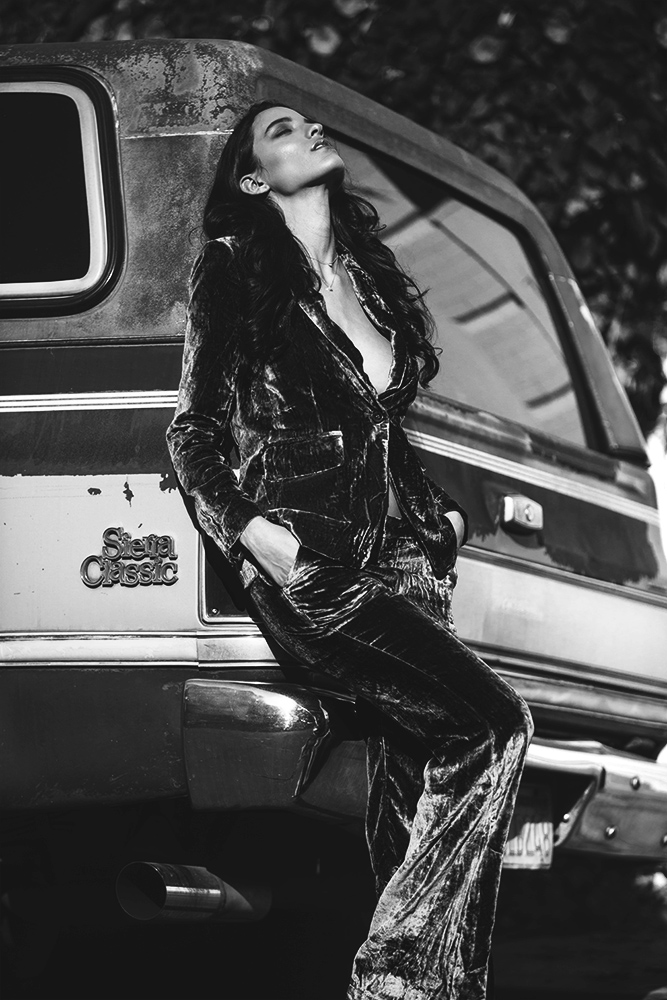 Black and white photo of a model posing next to a truck.