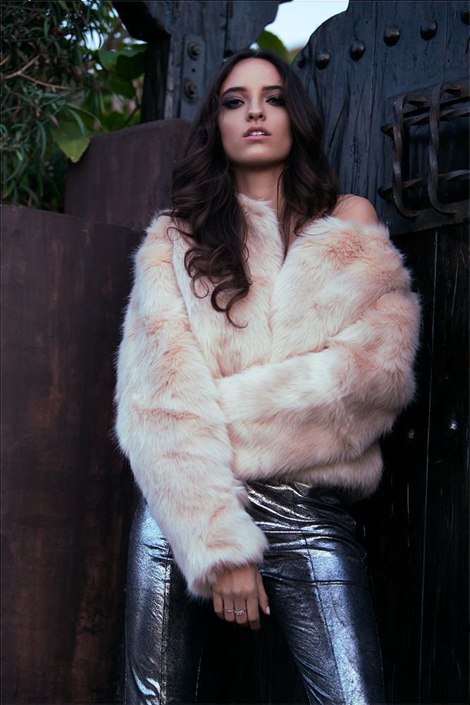 Model posing in a fake fur jacket in a backyard.