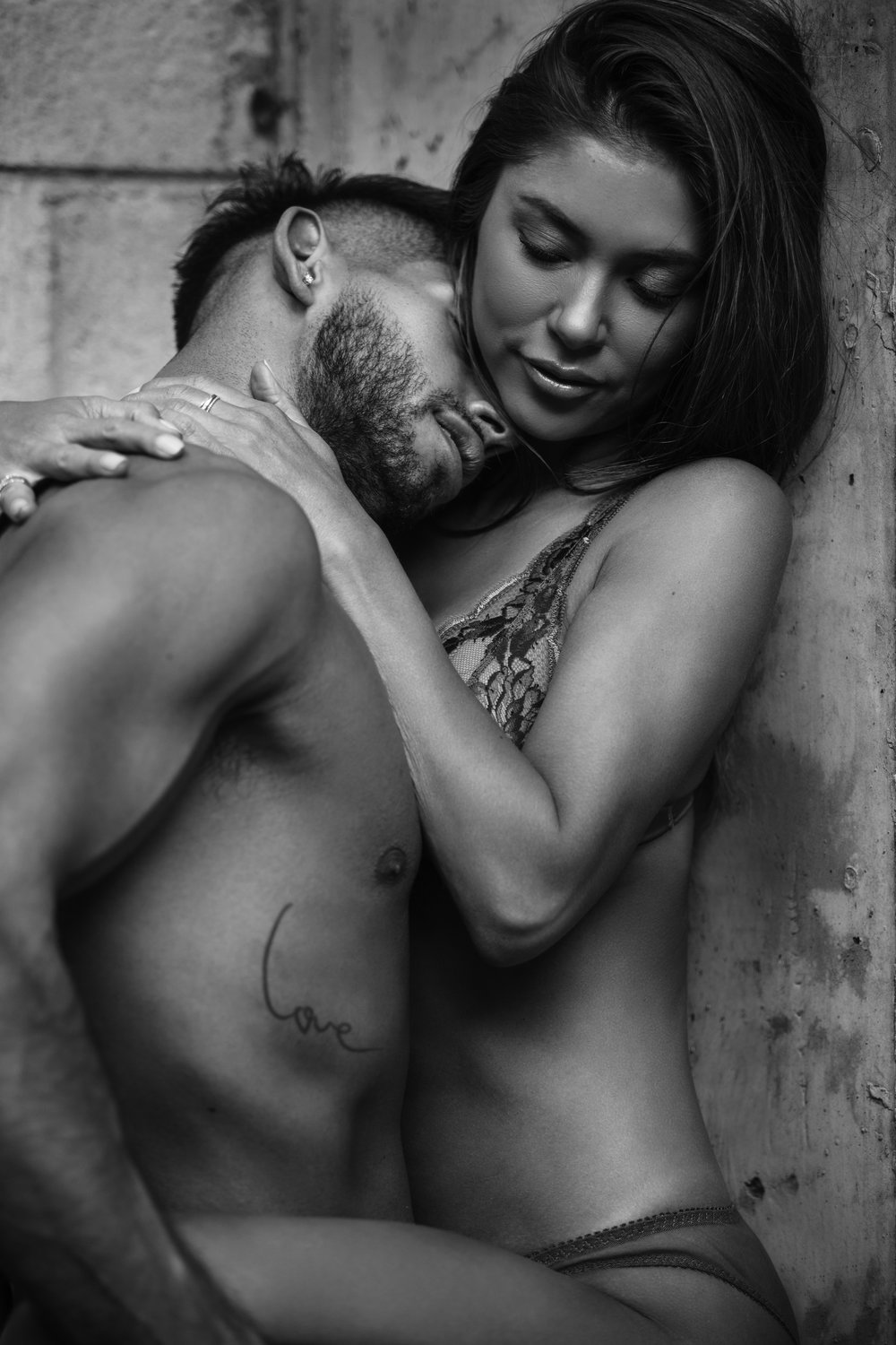 Male and female model posing intimately together. Black and white editorial photography.