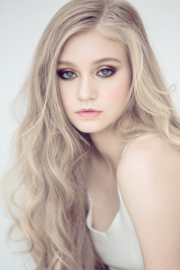 Portrait photography of a blonde female model in a studio in front of a white backdrop.