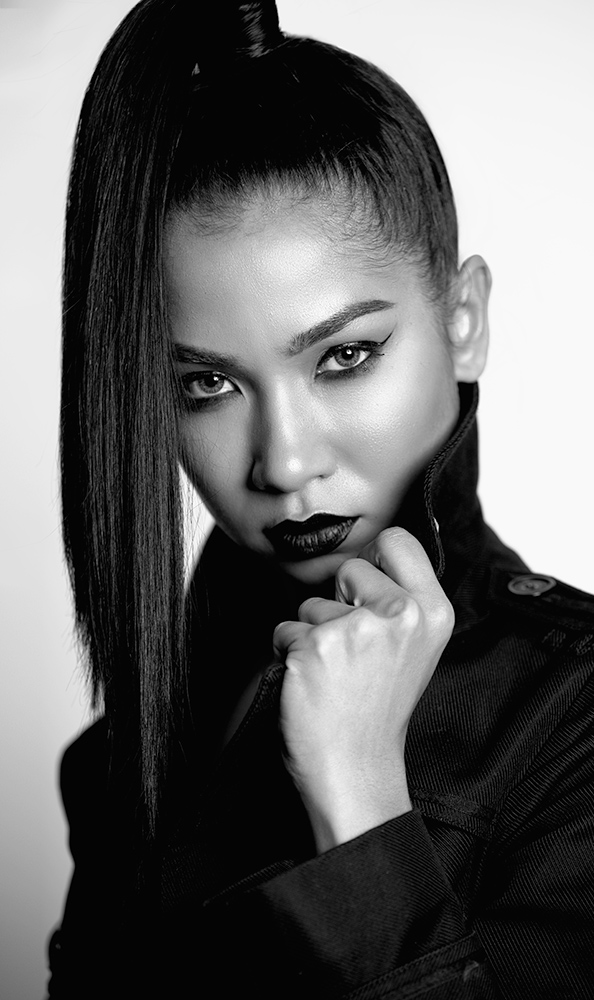 Black and white photo of a professional model wearing a black jacket with a high collar.