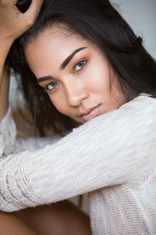 Beautiful model wearing a white sweater in a studio.