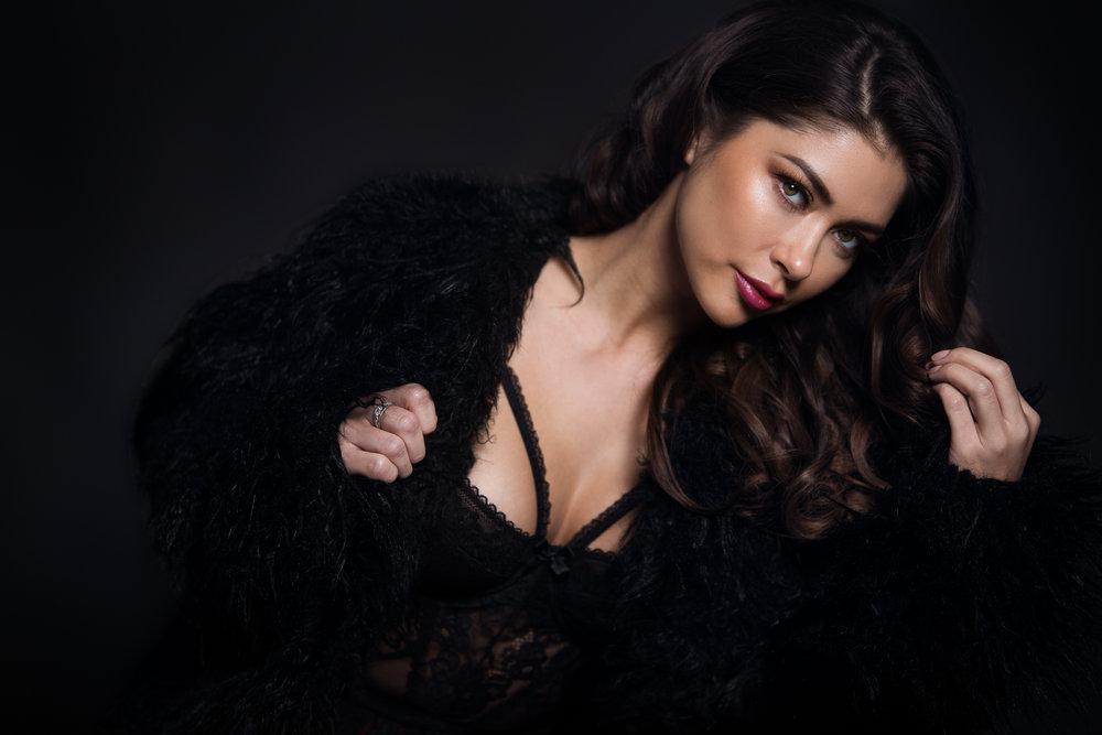 Model posing in a black jacket in front of a black backdrop.