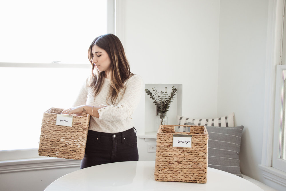 Girl organizing with three stripped baskets.